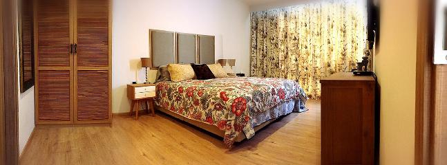 King size master bed with closet, and floor to ceiling windows.