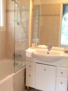 Ensuite bathroom with towel heater, bathtub, hairdryer, vanity mirror, towels and floor mats