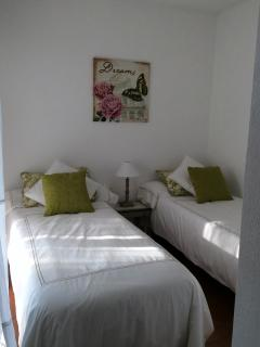 Guest bedroom with two single beds, linens, closet and direct access to terrace.