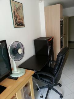Fan, office with office chair, refrigerator and view on kitchen, steel entrance door opened