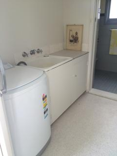 Laundry with dryer and spare bathroom through door