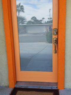 A Palm Springs welcome with a mid-century modern orange door!