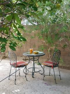 The secret garden with bistro table and seating for two - enjoy breakfast by the orange tree.