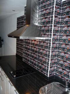 Kitchen with glass tiles, 2 ceramic electric cooking plates, hub and sink with cold and hot water