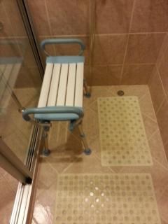 Seat in shower room and 2 plastic mats covers on floor for wheelchair users
