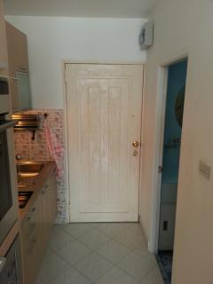 View on kitchen with steel entrance door and bathroom entrance door opened and main electric switch