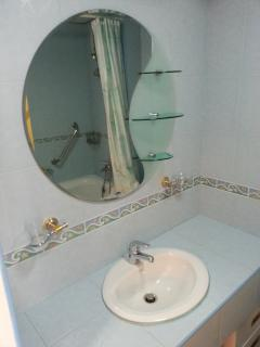 Round mirror and hand wash with cold and hot water in bathroom