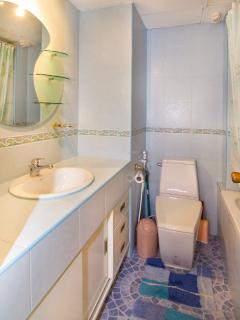 View into bathroom with toilette, round mirror and hand wash with cold and hot water