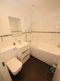 Bathroom; toilet, basin, bath with electric shower over