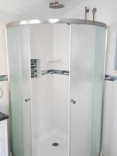 a large shower with rainfall shower head, a handheld and body jets and.....