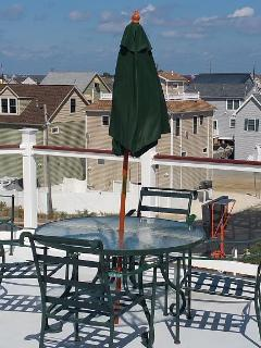 Roof deck table and view of ocean.