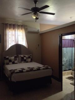 Our spacious bedroom with ceiling fan and air conditioning unit