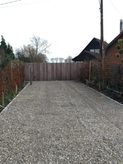 driveway with gate leading to secure parking