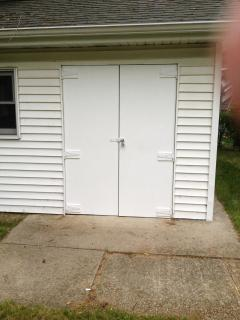 Outdoor shed holds dining and lounging furniture, BBQ grills-gas and Weber, older bikes, yard games,