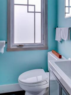 The bright blue bathroom is pristine.