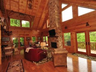 Large living area with natural light, stone fireplace, luxury furnishings, and open floor plan.
