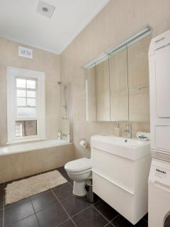 Large, bright bathroom features full sized bath, shower, Miele washing machine and dryer