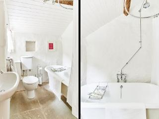 Bathroom with roll-top bath and exposed beam
