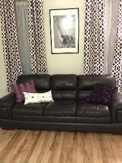 Beautiful brand new curtains behind this 100% leather sofa acompany by a matching love seat .