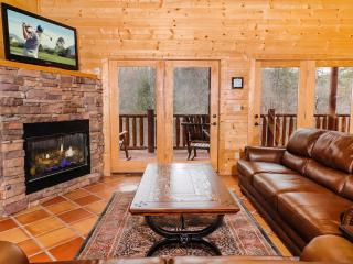 Family room with gas log fireplace, TV and comfy leather sofas