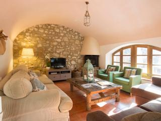 Relax in the living room with vaulted ceiling and characteristic stone wall