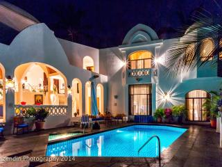 Pool, deck, jacuzzi and living room at night