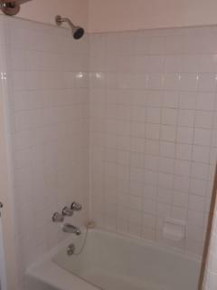 Full size bath tub & shower in the bathroom.