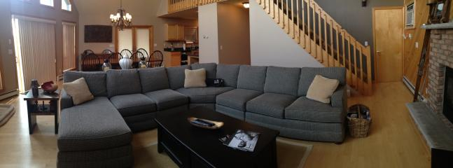Living room with flat screen TV, open layout to dining and gourmet kitchen
