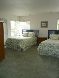 Master bedroom has two full sized beds, TV, two large  closets and a patio