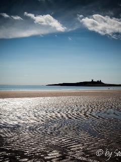 Dunstanburgh Castle across the bay