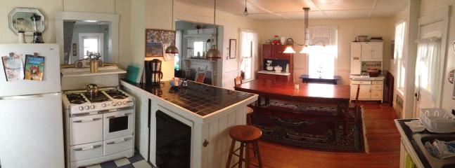 Panoramic view of kitchen through dining room and living room