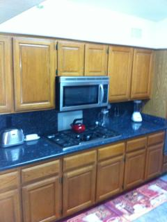 gas stove, microwave and double ovens in kitchen