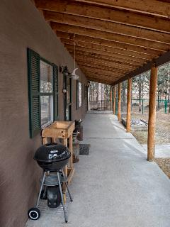 The front porch features a charcoal grill.