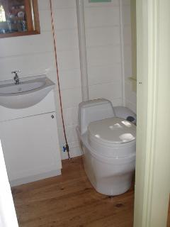 Interior bathroom with composting toilet and gravity fed rainwater sink/shower.