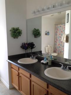 Master Bathroom showing Mirror, Twin Vanity Basins in Counter & Cupboards under