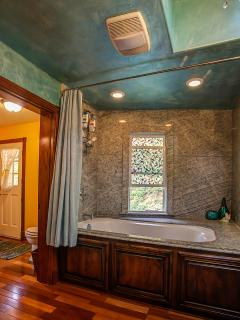Carribbean-themed bathroom with jacuzzi-style tub.