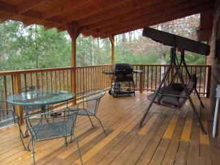 The large covered deck has swing, gas grill, table