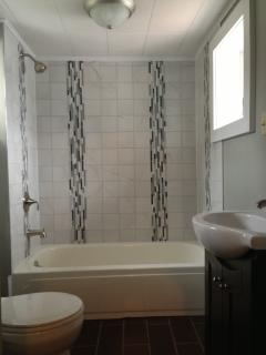The newly remodeled bathroom includes a new tile shower, floor, and new fixtures