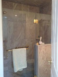 Glass shower enclosure in master bath. Grab bar in tiled shower.