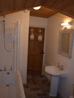 Pretty family bathroom with mini cathedral ceiling, bath and power shower