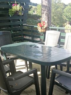Dining table and 6 chairs on the back deck.