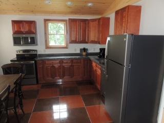 Fully equipped kitchen with new appliances, hardwood cabinets, large dining area.