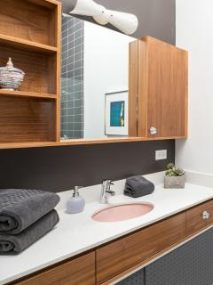 Second washroom features large walk-in shower, plush towels, and hairdryer.