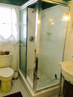 Glass enclosure with relaxing rain shower that can adjust to spray