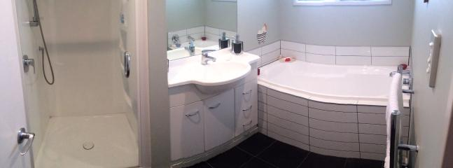 Modern bathroom with a great shower, bath heater and heated towel rail.
