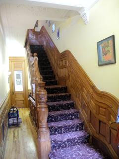 The decorated staircase is entirely made of cherry wood and fully carpeted