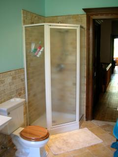 Large shower stall completes the 3rd-floor bathroom, with travertine floor