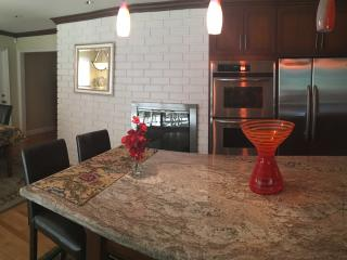 Huge granite center island perfect for gathering with 2 leather counter stools - beautiful kitchen