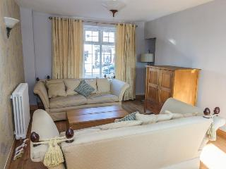 Sitting room with 3D TV, twin sofas and arm chair overlooking walled garden.