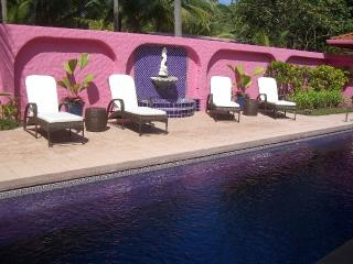 Enjoy lounge chairs and a fountain beside the private pool